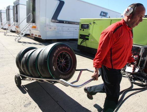 Un mécanico de bridgestone tira de un carro con cuatro neumáticos slicks para rodar con la pista seca.  Foto: J. C. Toro