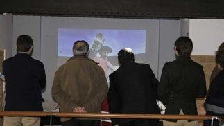 Varias personas viendo un audiovisual de fotografías de Fito Carreto que se proyecta como complemento de la exposición  Foto: Andres Mora