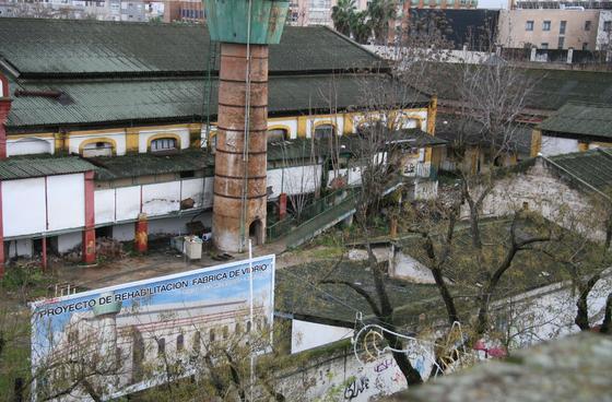 Cartel que anuncia el proyecto de rehabilitación a la que será sometida la antigua fábrica con la fachada principal de la misma, totalmente deteriorada, al fondo.  Foto: Victoria Hidalgo