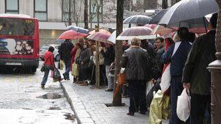 Decenas de personas se protegen de la lluvia mientras esperan el autobús.  Foto: J. C. Vázquez, B. Vargas y A. Pizarro