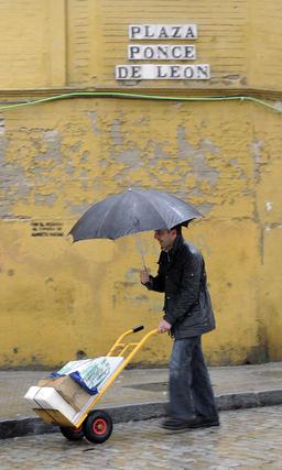 Un hombre empuja una carretilla con una mano mientras con la otra sujeta un paragüas para evitar mojarse.  Foto: J. C. Vázquez, B. Vargas y A. Pizarro