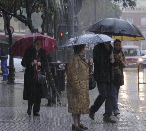 Las fuertes lluvias no han evitado que los ciudadanos se mojen a pesar de llevar paragüas.  Foto: J. C. Vázquez, B. Vargas y A. Pizarro