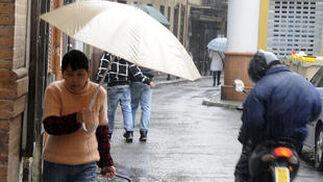 Una mujer se dirige a hacer la compra a pesar de las precipitaciones.  Foto: J. C. Vázquez, B. Vargas y A. Pizarro