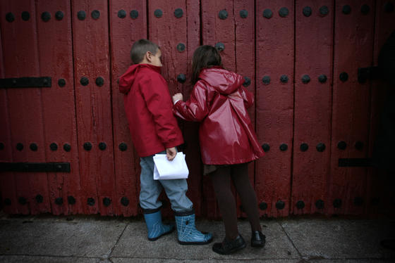 Un niño y una niña se asoman por la abertura de la puerta para ver si descubren al Heraldo.  Foto: Juan Carlos Muñoz