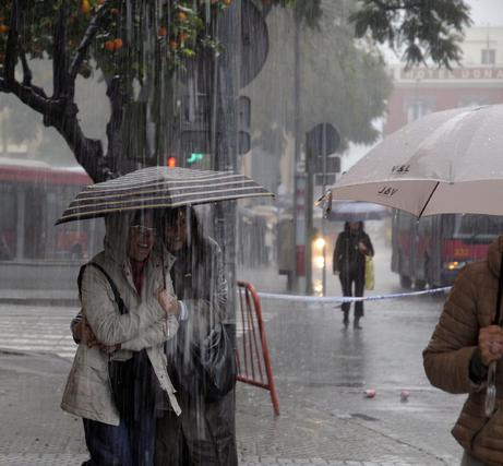 Dos mujeres se cobijan de la lluvia en un mismo paragüas.  Foto: J. C. Vázquez, B. Vargas y A. Pizarro