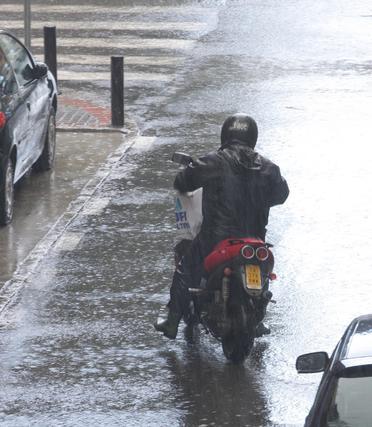 Un motorista circula con precaución protegido de la lluvia con un impermeable.  Foto: J. C. Vázquez, B. Vargas y A. Pizarro