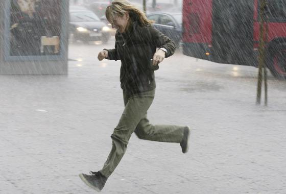 Una mujer corre en busca de un lugar para protegerse de la lluvia.  Foto: J. C. Vázquez, B. Vargas y A. Pizarro