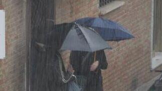 Dos personas conversan, protegidos con sus paragüas, mientras llueve.  Foto: J. C. Vázquez, B. Vargas y A. Pizarro