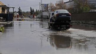 Una grúa trasnportando un vehículo atraviesa uno de los charcos provocados por las lluvias.  Foto: J. C. Vázquez, B. Vargas y A. Pizarro