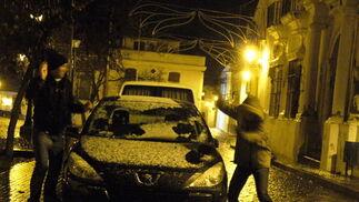 Dos jóvenes juegan con la nieve caída sobre un coche en el municipio serrano de Cazalla de la Sierra.  Foto: B.Vargas/Juan Carlos Vázquez