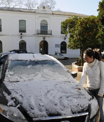 Una joven limpia la nieve acumulada sobre su coche.  Foto: B.Vargas/Juan Carlos Vázquez