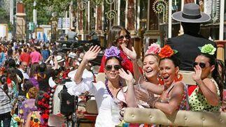 Jóvenes vestidas de gitana saludan desde un carro.  Foto: Pascual
