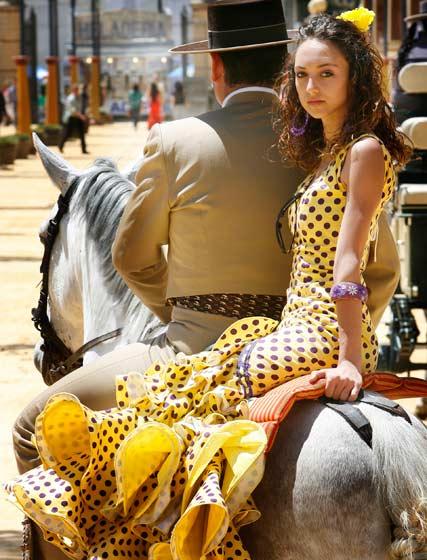 Una jóven vestida de gitana se pasea a lomos de un caballo por el Real.  Foto: Pascual