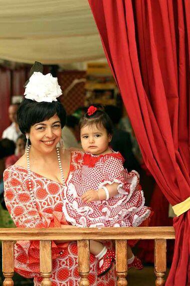 Inma y su hija María contemplan la belleza de la Feria asomadas entre las cortinas de caseta  Foto: M.A. González- Pascual