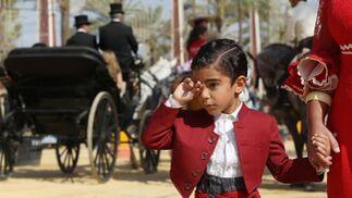 Un niño vestido de corto se frota los ojos agarrado de la mano de su madre, vestida de gitana.   Foto: M.A. González- Pascual