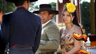 Dos caballistas -uno de ellos con una mujer vestida de gitana a la grupa- intercambian impresiones en el Real.  Foto: miguel ángel gonzález