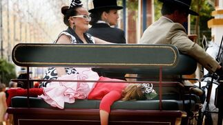 Una niña vestida de gitana, derrotada ya a estas alturas de la Feria, dormida en un enganche.   Foto: Pascual