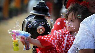 Una pequeña vestida de flamenca se divierte haciendo pompas de jabón.  Foto: miguel ángel gonzález