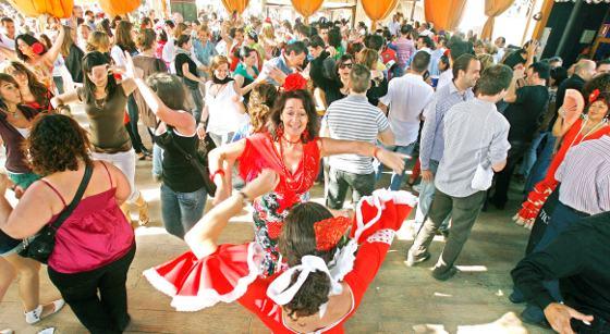 Dos jóvenes bailan sevillanas entre el gentío.  Foto: Pascual