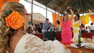 Dos mujeres bailan sevillanas en el templete municipal mientras una tercera las mira.  Foto: miguel ángel gonzález