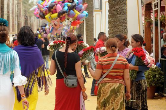 Unas vendedoras de claveles con sus niños, algo que además está prohibido.  Foto: pascual