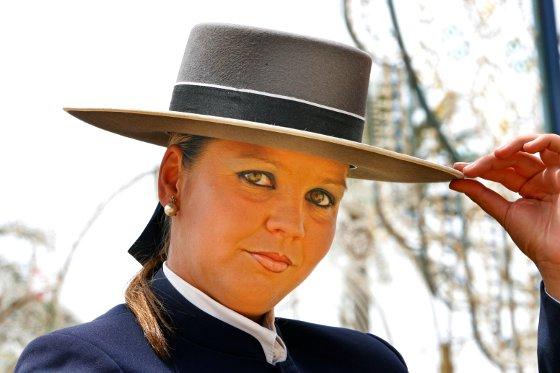Una guapa joven posa en el recinto feria sosteniendo su sombrero de ala ancha  Foto: pascual