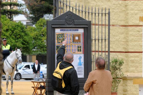 Unos turistas buscan información en un mapa que indica la ubicación de las casetas.