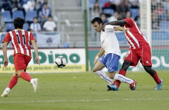 Mbami agarra a Ayoze en la disputa por un balón en la zona central del terreno de juego.   Foto: EFE