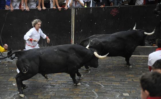 El primer encierro de 2012 finaliza con una cornada en el primer tramo y la entrada en la plaza de un toro con un mozo en una de sus astas.  Foto: EFE / Reuters