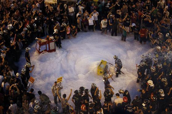 Bomberos llenan el suelo de espuma en la protesta de Barcelona.  Foto: EFE · Reuters · AFP