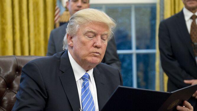 Donal Trump leyendo una orden ejecutiva.