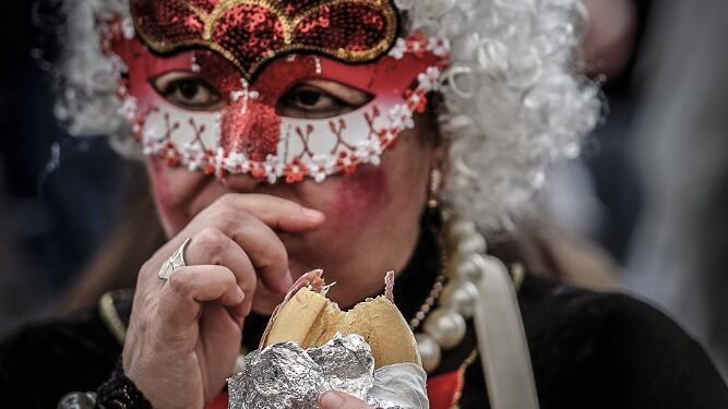 Una mujer, ataviada con un antifaz, se come un bocadillo durante el Carnaval.
