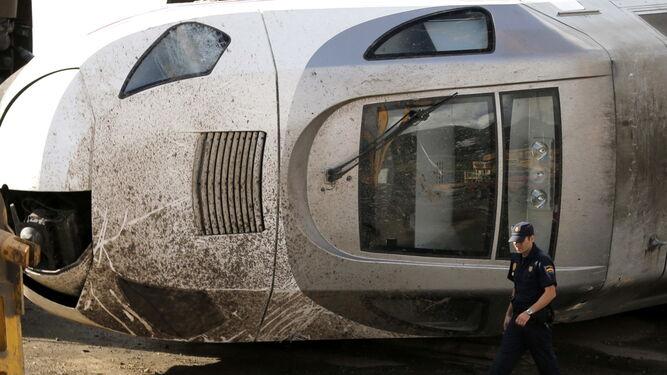 Un policía pasa por delante de la cabina del tren siniestrado.