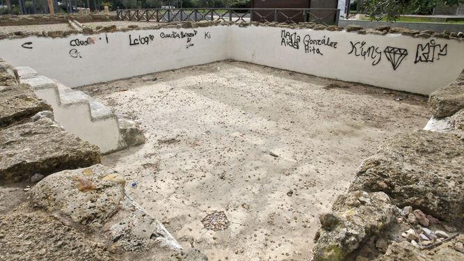 1. Uno de los patios de la antigua casa romana, cubierta por pintadas. 2 y 5. Daño también en una de las columnas y en una valla del mismo complejo arqueológico. 3. El acueducto, con la marca de los vándalosa. 4. La placa de la memoria histórica.