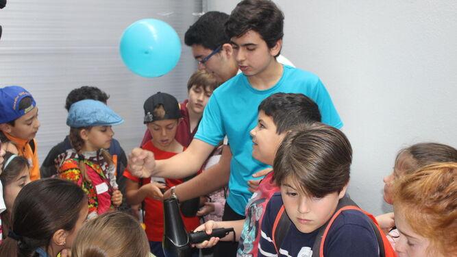 Alumnos de Secundaria explican a los de Primaria uno de los experimentos presentados ayer en la II Feria de la Ciencia.