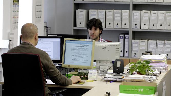 Dos funcionarios examinando unos documentos en sus ordenadores.