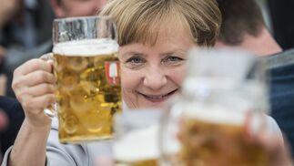 Angela Merkel brinda con una jarra de cerveza.