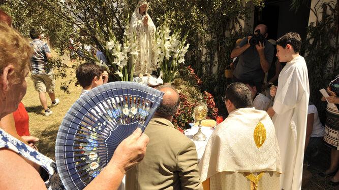Un hombre enseña a una pequeña uno de los altares de Zahara.