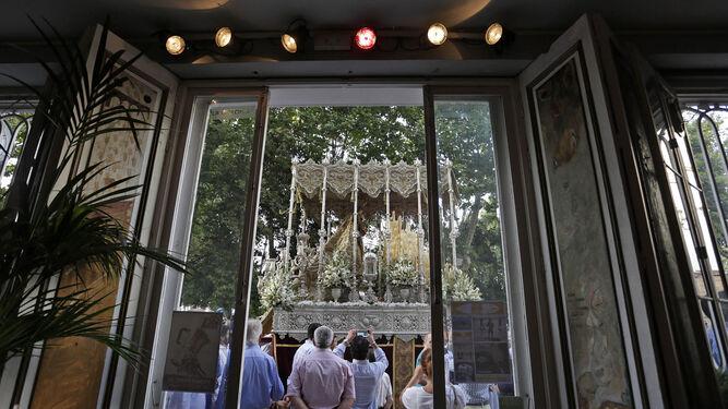 El paso de palio de la Virgen del Carmen pasa por delante de un establecimiento hotelero de la zona de la Alameda.