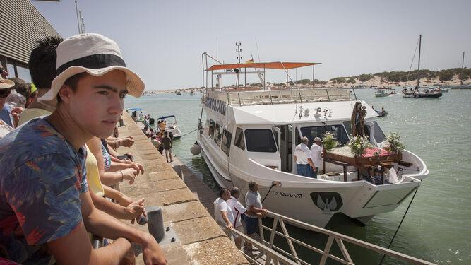 Un joven ante el barco en el que navegó la Virgen 'Atunera'.