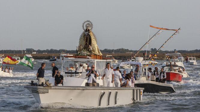La Virgen del Carmen de Gallineras surca sobre una embarcación con una estela de de barcos el caño de Sancti Petri cuando ya regresa de La Magdalena.