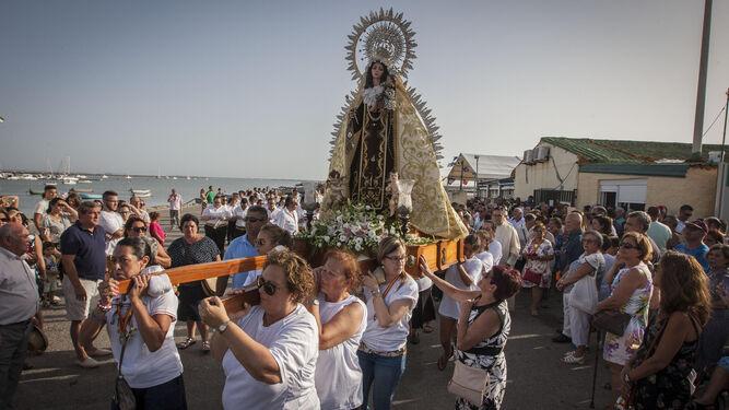 Un grupo de mujeres porta la parihuela de la Señora del Mar, en el muelle de Gallineras.