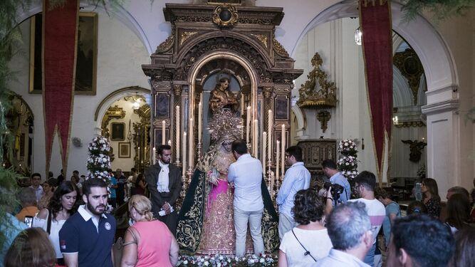 Mucho público en el interior de San Francisco, con el besamano en primer término de la Virgen de la Esperanza del Amor.