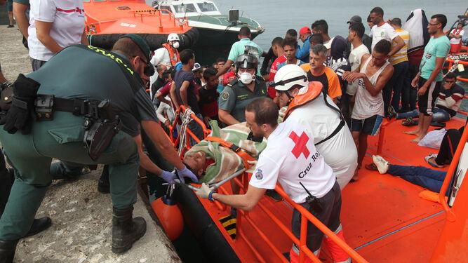 Miembros de la Guardia Civil, la Cruz Roja y Salvamento Marítimo participan en el traslado a tierra de uno de los migrantes rescatados.