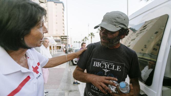 Ana María, una de las voluntarias de Cruz Roja, reparte un bocadillo y una botella de agua a Carlos, un sin techo de la capital.