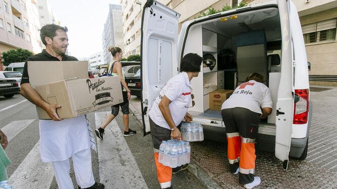 Un cocinero ayuda a cargar el coche de Cruz Roja de alimento para el reparto.