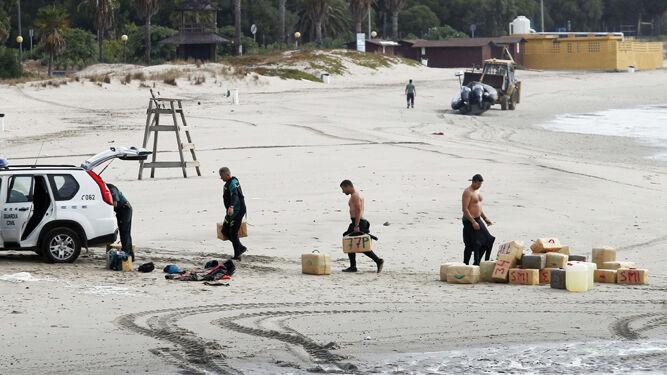 Agentes de la Guardia Civil transportando fardos incautados en una playa de la provincia.
