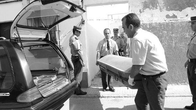 Empleados de una funeraria trasladan el cadáver de Antonio Romero Núñez por la puerta trasera de su vivienda de la calle Álava