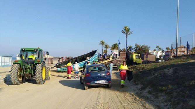 Operarios retiran esta mañana la patera de la arena