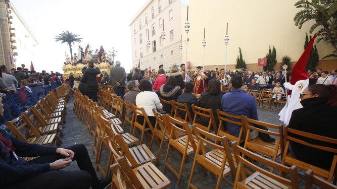 Las sillas de Arquitecto Acero, que se 'estrenaban' este año, con el paso de misterio de La Borriquita al fondo.